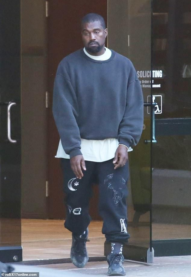 Kanye West looks downbeat as he steps out of his office in his new Adidas Yeezy Boost 700 sneakers