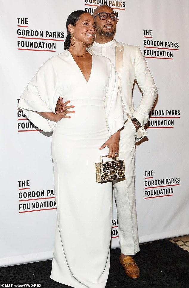 Alicia Keys' husband Swizz Beatz puts his hand on her waist as she models plunging dress