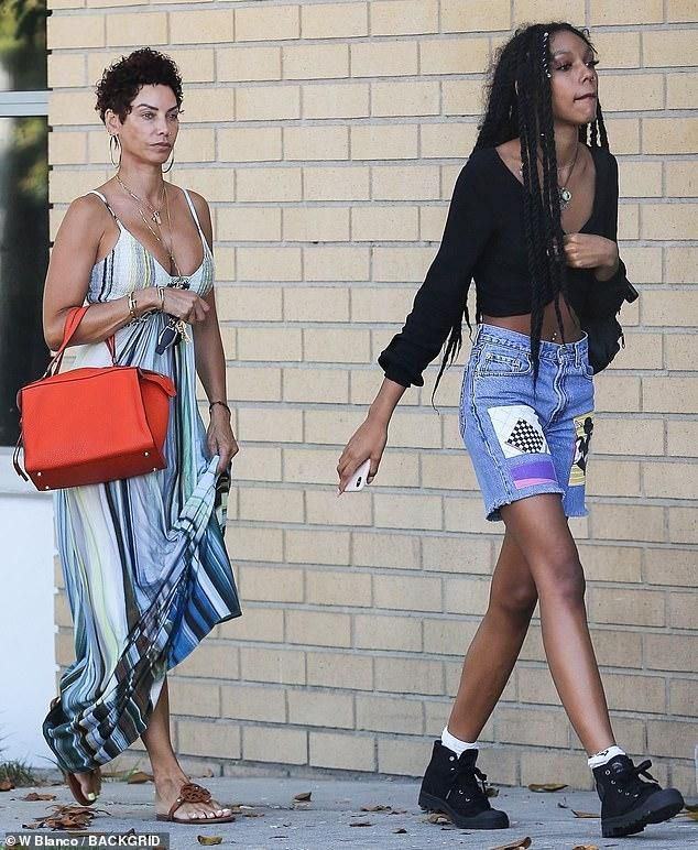 Nicole Murphy, 51, rocks busty striped sundress on an afternoon outing with daughter Zola, 19